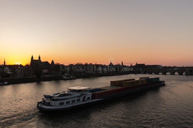 Vrachtschip dat met containers wordt geladen die over de rivier Maas reizen stock afbeeldingen