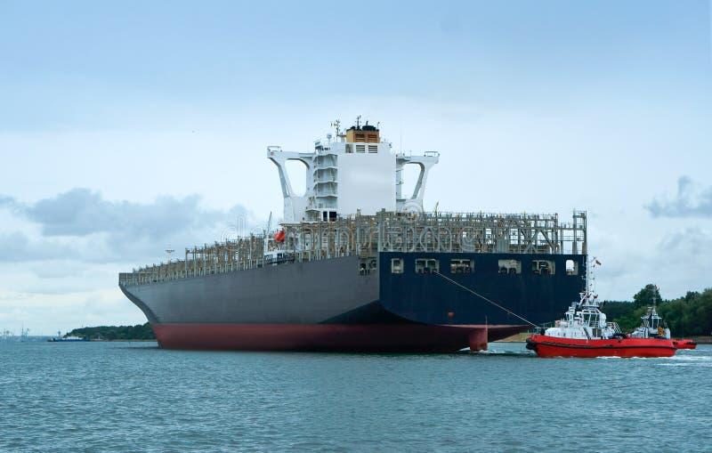 Vrachtschip door twee wachten, leeg containerschip, overzees vrachtschip wordt begeleid dat royalty-vrije stock afbeelding