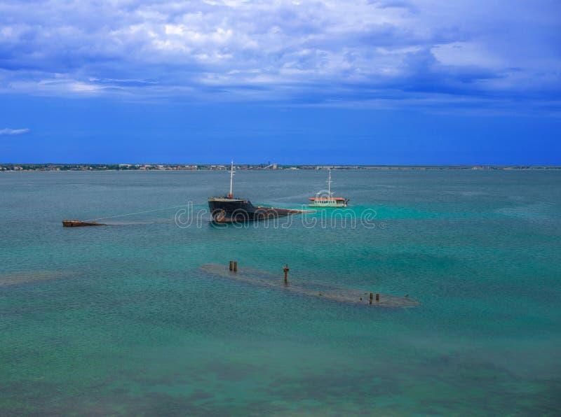 Vrachtschip en aken dichtbij de kust is vastgelopen die royalty-vrije stock afbeelding