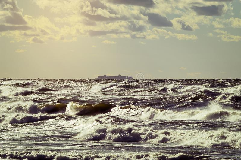 Vrachtschipsilhouet op de horizon Groot containerschip die door stormachtige golven van de Oostzee varen stock afbeelding