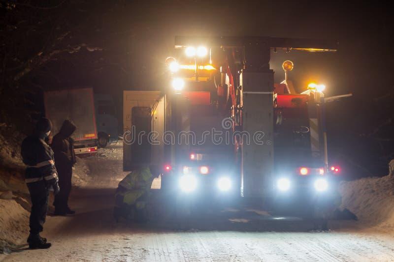 Vrachtverkeerongeval bij nacht, op een sneeuw de winterweg Trekt de sterk verlichte Wrecker-vrachtwagen een vrachtwagen uit sneeu royalty-vrije stock fotografie