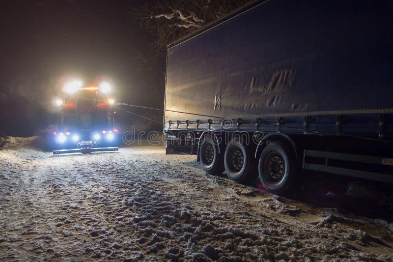 Vrachtverkeerongeval bij nacht, op een sneeuw de winterweg Trekt de sterk verlichte Wrecker-vrachtwagen een vrachtwagen uit sneeu stock afbeeldingen