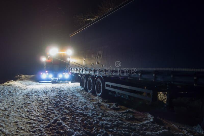 Vrachtverkeerongeval bij nacht, op een sneeuw de winterweg Trekt de sterk verlichte Wrecker-vrachtwagen een vrachtwagen uit sneeu royalty-vrije stock afbeelding