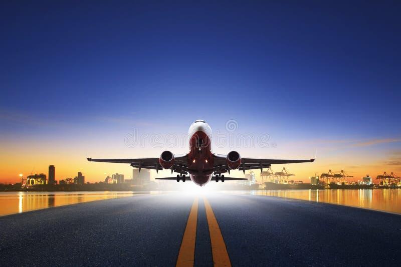 Vrachtvliegtuigstart van luchthavenbanen tegen de rug van de schiphaven stock afbeelding