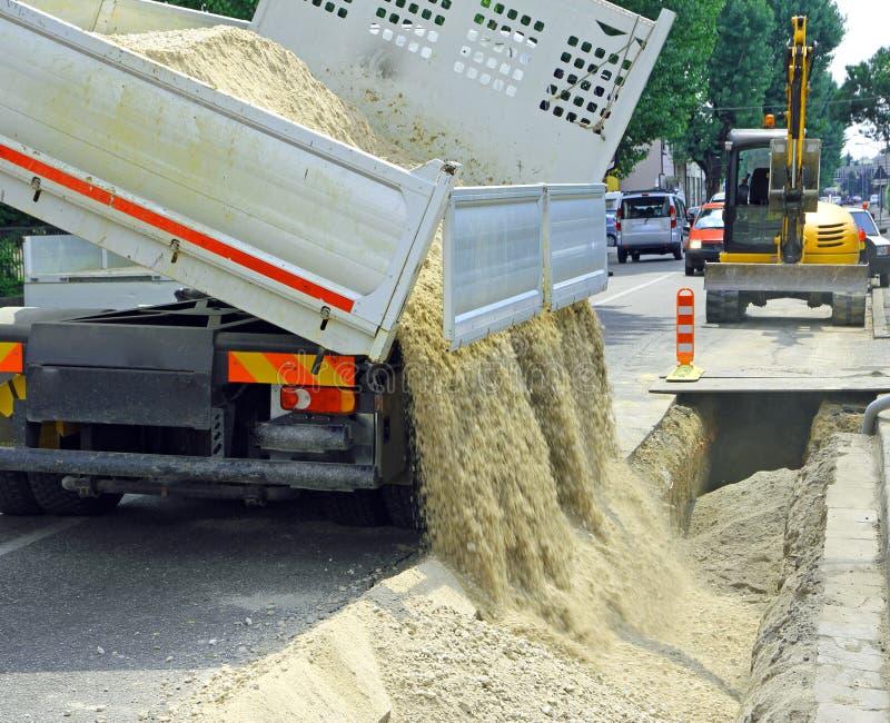 Vrachtwagen in de uitgraving na het leggen van ondergrondse elektrische cabine stock foto