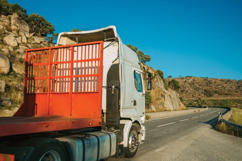 Vrachtwagen die een andere vrachtwagen dragen door weg op heuvelig landschap stock afbeelding