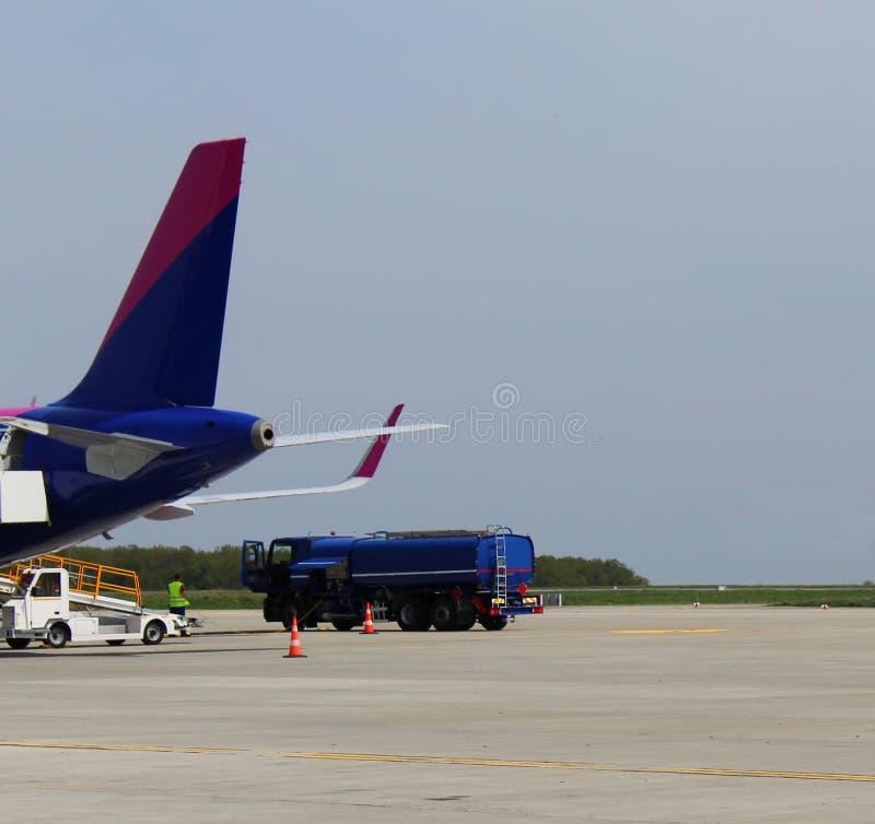 Vrachtwagen die een vliegtuig op de luchthaven bijtanken stock fotografie