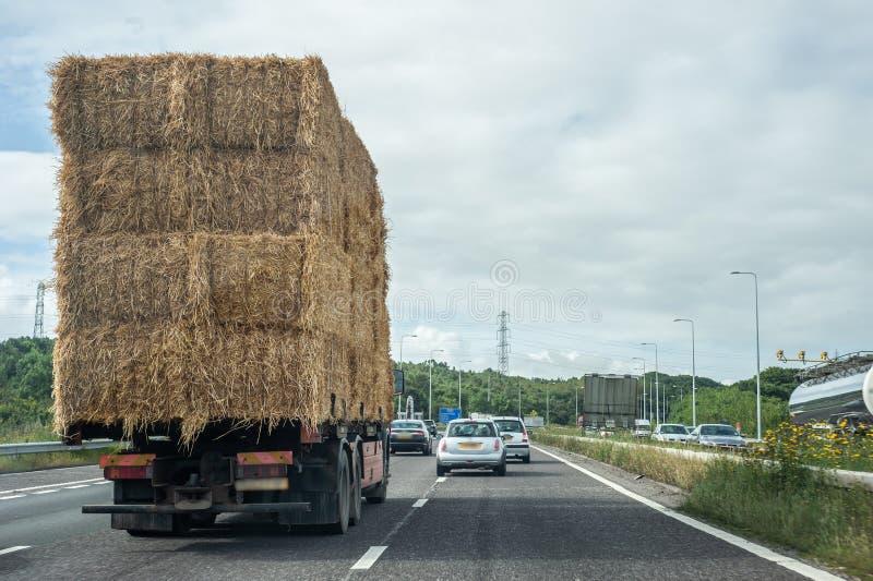 Vrachtwagen die hooibalen op een weg vervoeren stock fotografie