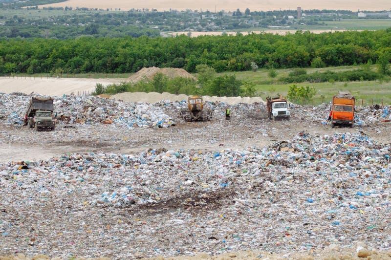 Vrachtwagen die in stortplaats met vogels werken die voedsel zoeken Huisvuil op de stadsstortplaats Grondverontreiniging Milieuvr royalty-vrije stock foto