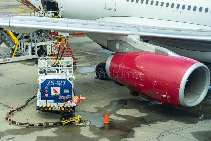 Vrachtwagen met brandstoftank op baan De brandstofvrachtwagen tankt aan het passagiersvliegtuig bij Arbeiders die Zakken laden in stock afbeeldingen