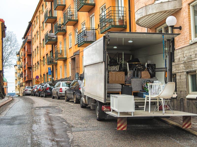 Vrachtwagen met dozen en ander materiaal op de straat Het bewegen zich aan de nieuwe flat royalty-vrije stock afbeeldingen