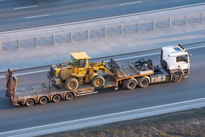 Vrachtwagen met een lang aanhangwagenplatform voor het vervoeren van zware machines, geladen tractor met een emmer Het vervoer va stock fotografie