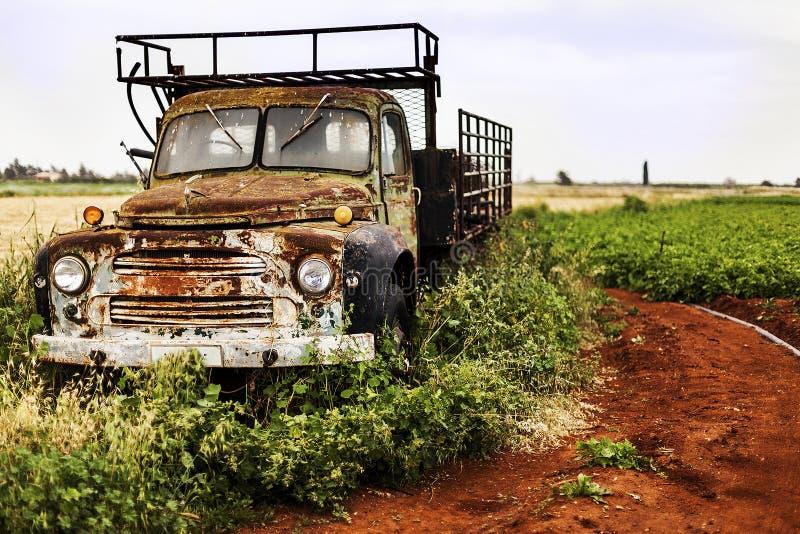 Vrachtwagen op het gebied is en wordt verlaten geroest dat stock fotografie