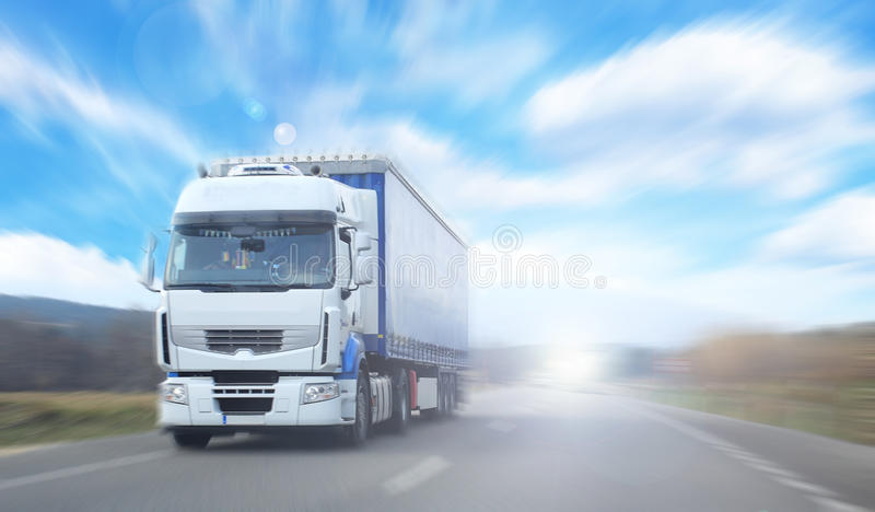 Vrachtwagen op onscherpe weg over blauwe bewolkte hemelbackgrou stock fotografie