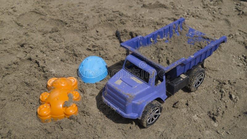 Vrachtwagen van kinderen laadde met zand, ligt naast zandvormen royalty-vrije stock afbeelding