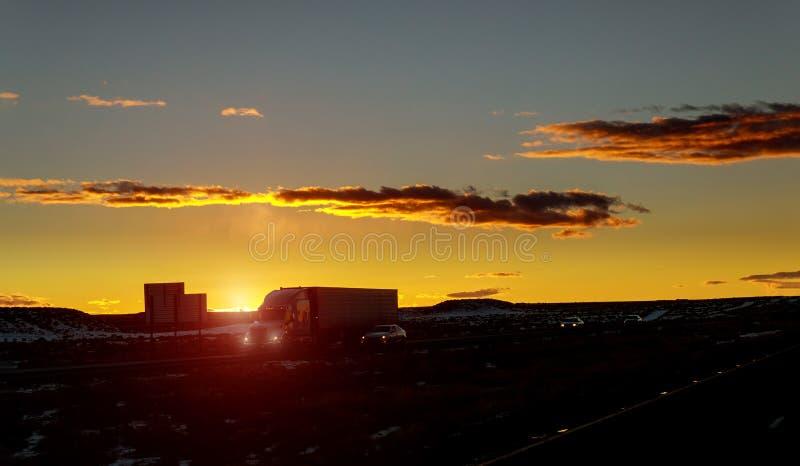 Vrachtwagenauto's op een weg bij zonsopgang met mooie zon op achtergrond royalty-vrije stock afbeelding
