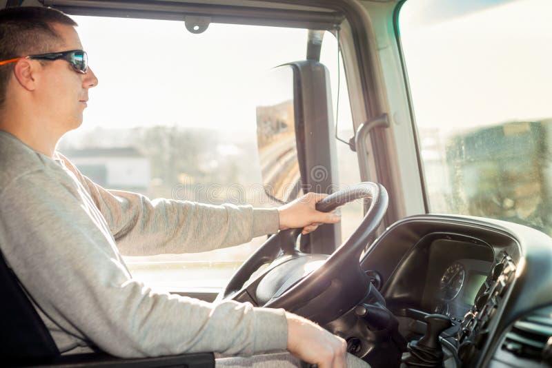 Vrachtwagenchauffeur in de cabine stock afbeelding