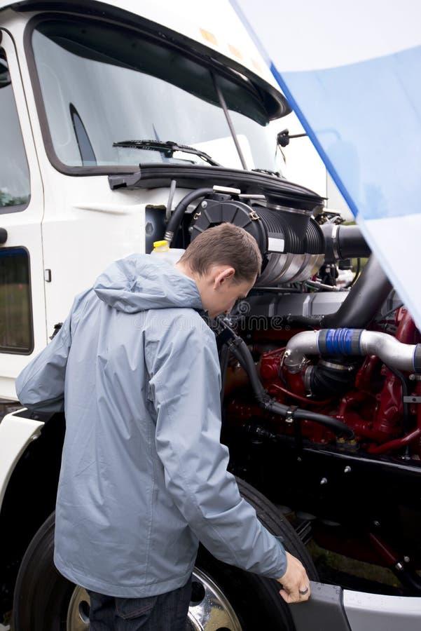 Vrachtwagenchauffeur die de semi vrachtwagen van de verrichtingsmotor met open kap controleren royalty-vrije stock afbeelding