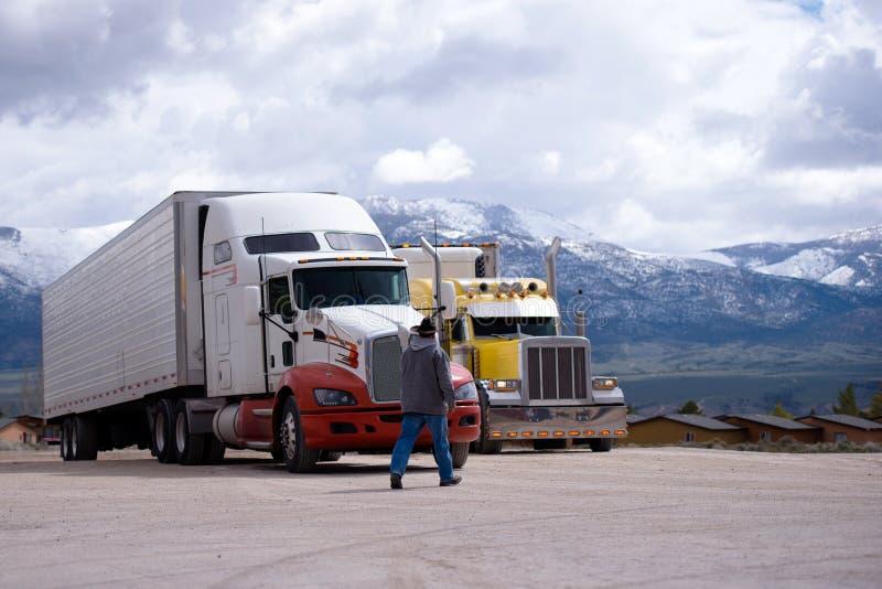 Vrachtwagenchauffeur die naar zijn semi vrachtwageninstallatie gaan op parkeerterrein stock fotografie