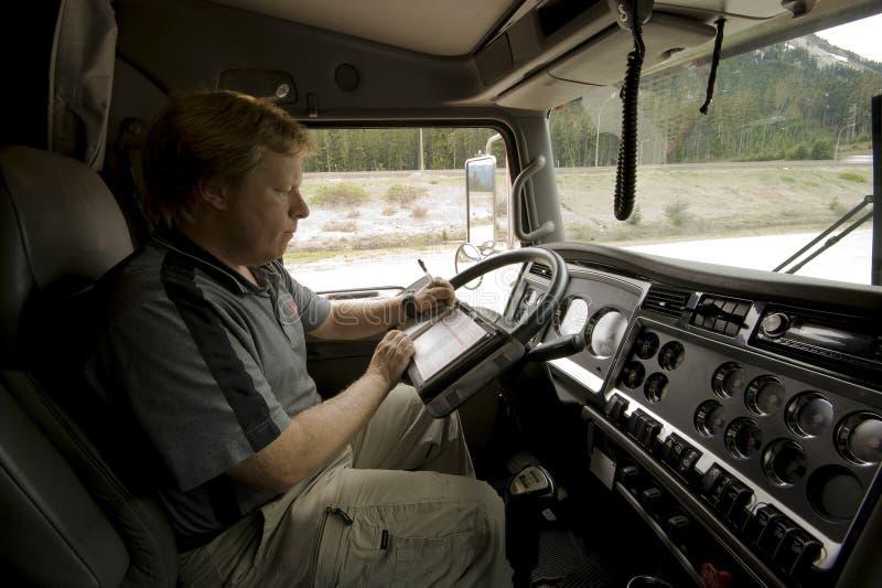 Vrachtwagenchauffeur die zijn logboek bijwerkt royalty-vrije stock fotografie