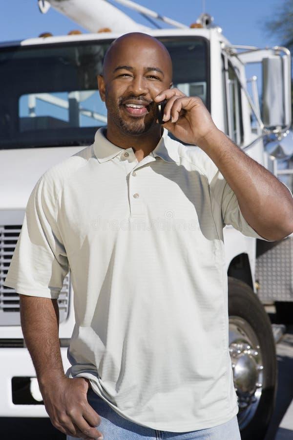 Vrachtwagenchauffeur On Phone In Front Of een Vrachtwagen stock afbeeldingen