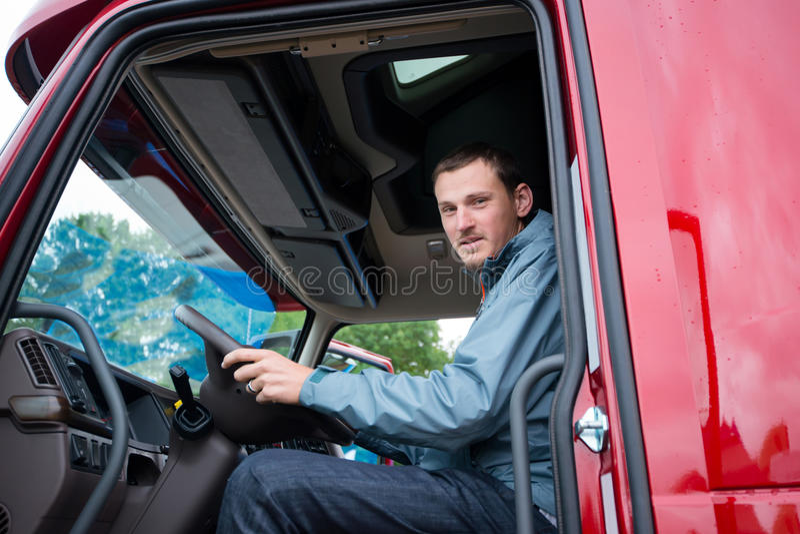 Vrachtwagenchauffeur in semi vrachtwagencabine met modern dashboard royalty-vrije stock foto