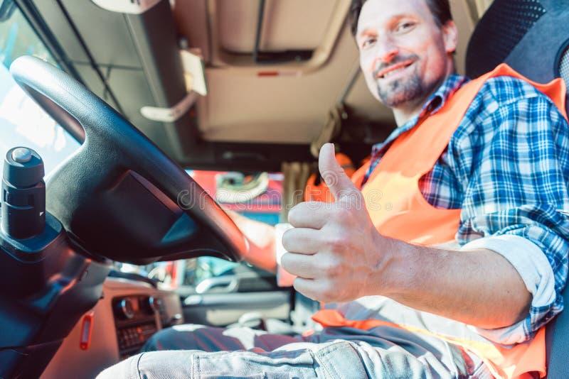 Vrachtwagenchauffeurzitting in cabine die duim-omhoog geven royalty-vrije stock fotografie