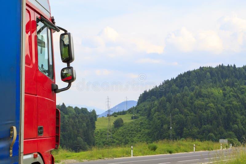vrachtwagenritten op de weg door de zomerbos, weiden en FI royalty-vrije stock fotografie