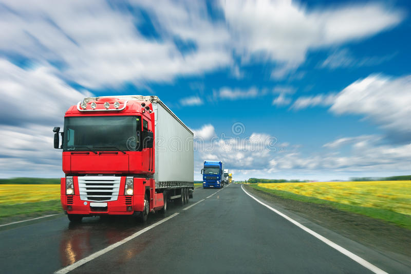 Vrachtwagens bij landweg bij zonnige dag royalty-vrije stock foto
