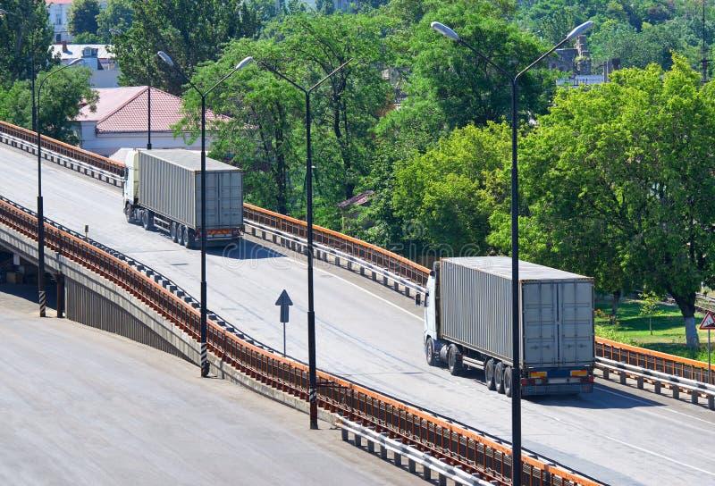 Vrachtwagens die de brug, ladingsvervoer, levering uitgaan en concept, groene bomen op achtergrond verschepen stock foto