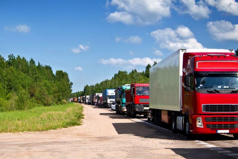 Vrachtwagens in een rij. De Opstopping van de weg. stock foto's