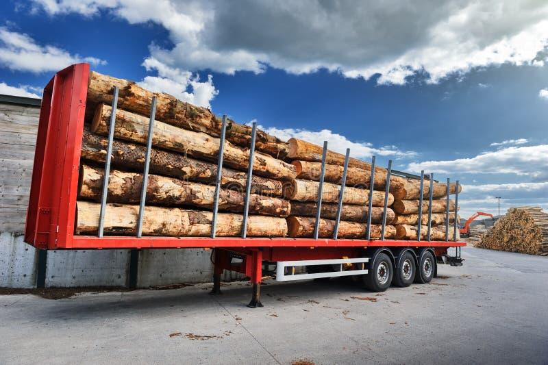 Vrachtwagens met houten logboeken worden belast die op levering wachten die royalty-vrije stock afbeelding