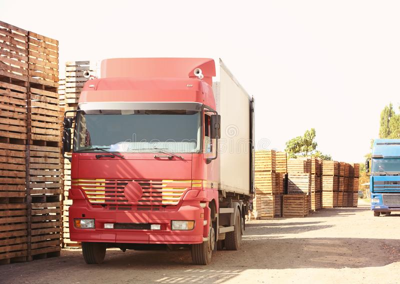 Vrachtwagens naast lege houten kratten royalty-vrije stock afbeeldingen