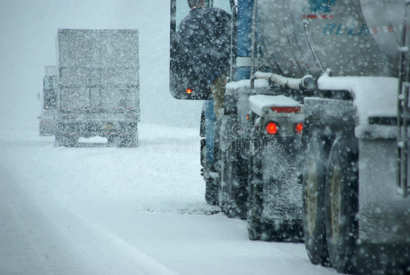Vrachtwagens op de winterweg tijdens sneeuwstorm stock afbeeldingen