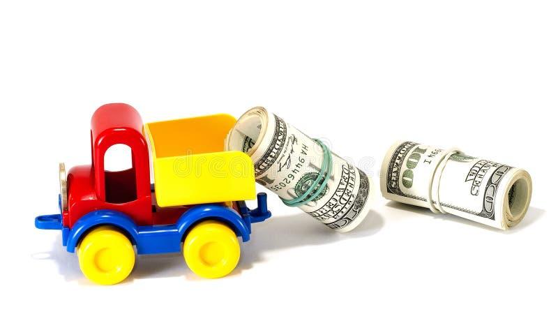 Vrachtwagenstuk speelgoed op de weg van geld stock fotografie