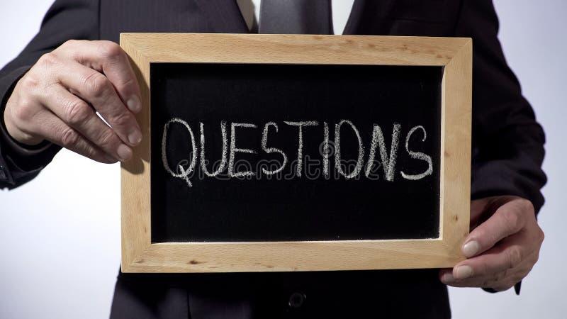 Vragen op bord, het teken van de bedrijfspersoonsholding, FAQ, raad worden geschreven die royalty-vrije stock afbeeldingen