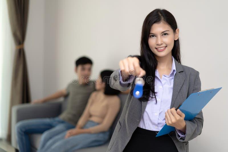Vrai agent immobilier avec la famille asiatique obtenant la nouvelle maison Affaires c image stock