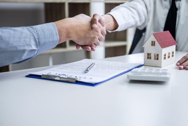 Vrai agent immobilier et clients se serrant la main célébrant ensemble le contrat de finition après la signature au sujet de l'as photographie stock libre de droits