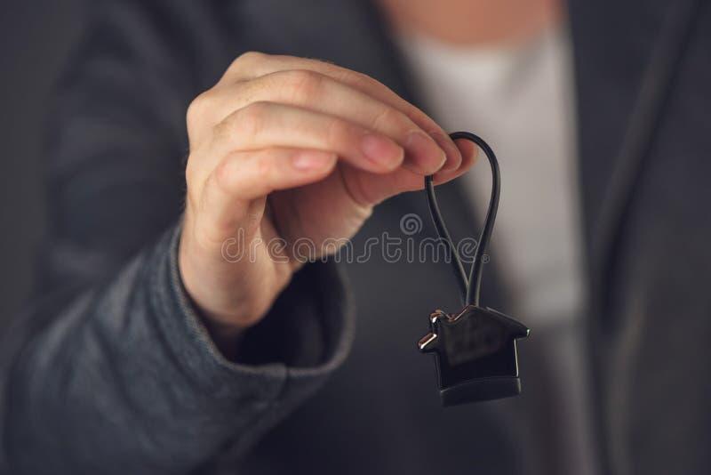 Vrai agent immobilier femelle avec le porte-clés de modèle de maison photos stock