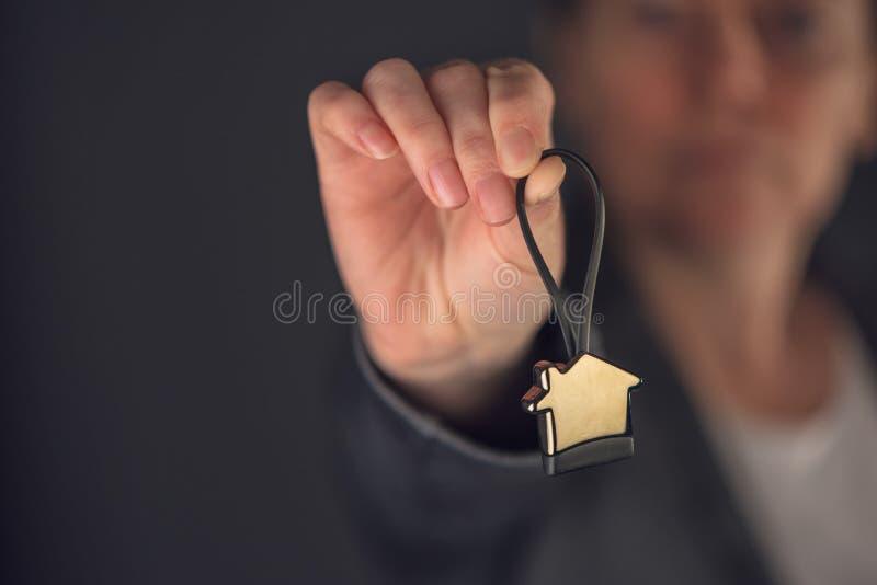 Vrai agent immobilier femelle avec le porte-clés de modèle de maison photographie stock libre de droits