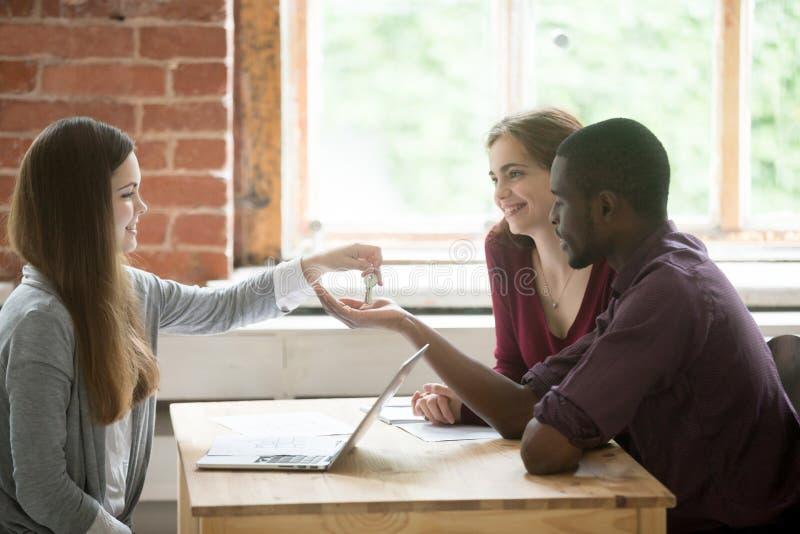 Vrai agent immobilier femelle donnant des clés à de jeunes couples images libres de droits