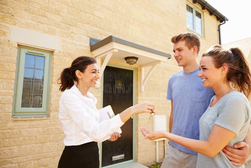 Vrai agent immobilier femelle donnant des clés à de nouveaux propriétaires photos stock