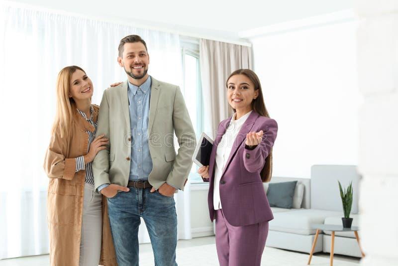 Vrai agent immobilier femelle montrant la nouvelle maison pour coupler photographie stock libre de droits