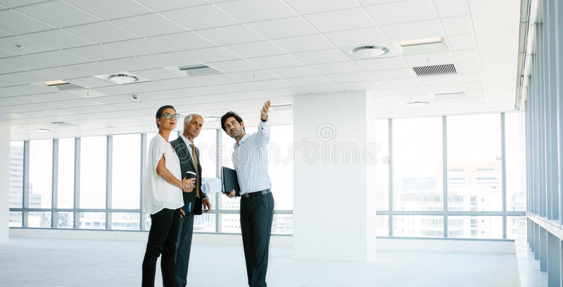 Vrai agent immobilier montrant de nouveaux bureaux aux clients images libres de droits