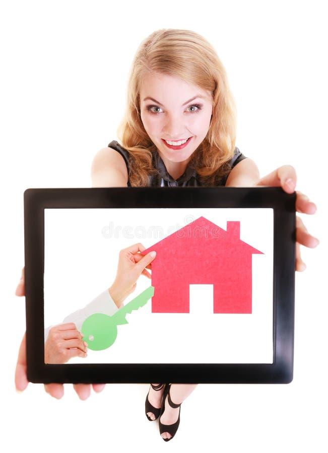 Vrai agent immobilier montrant la maison de papier sur le comprimé images stock