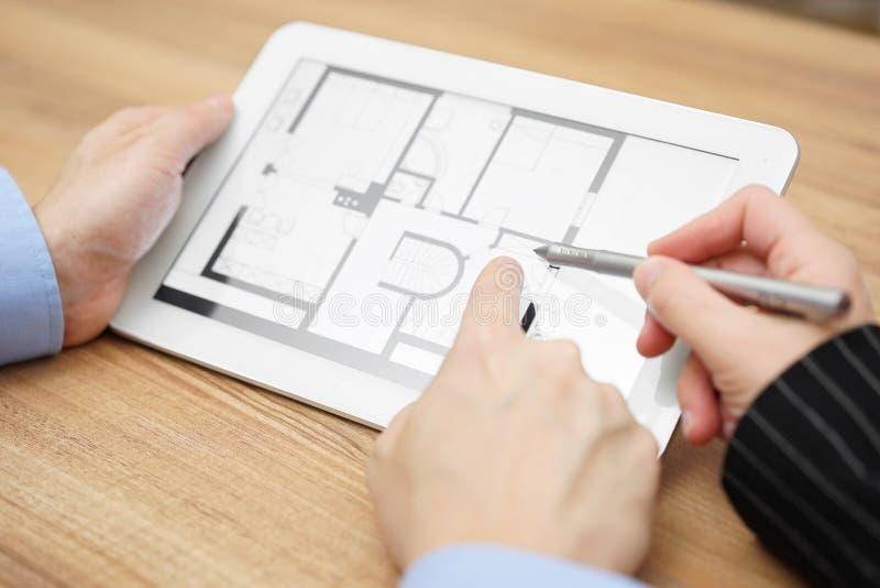 Vrai agent immobilier montrant la projection à la maison sur la tablette image libre de droits