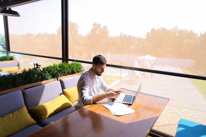 Vrai agent immobilier parlant par le smartphone et travaillant avec l'ordinateur portable images libres de droits