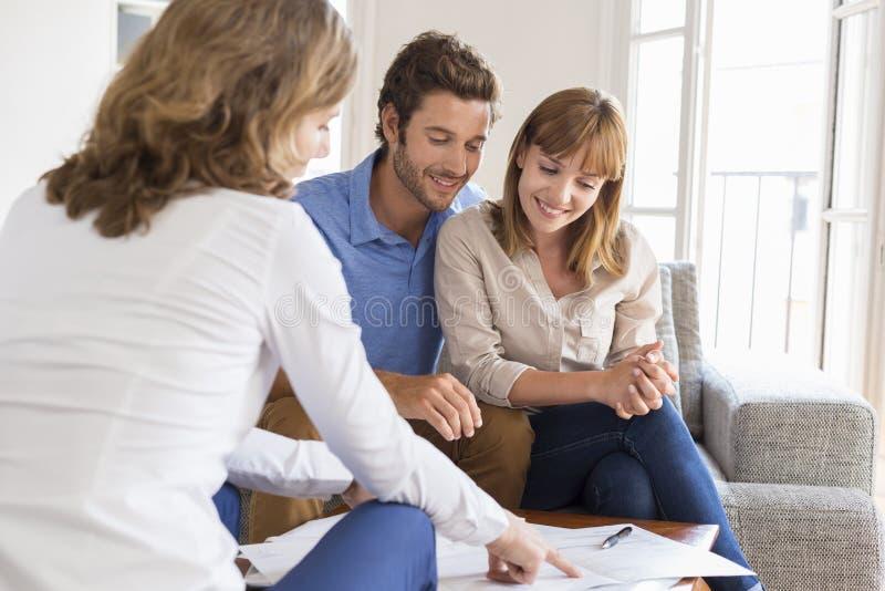 Vrai agent immobilier présentant un contrat pour l'investissement de maison à un couple images libres de droits