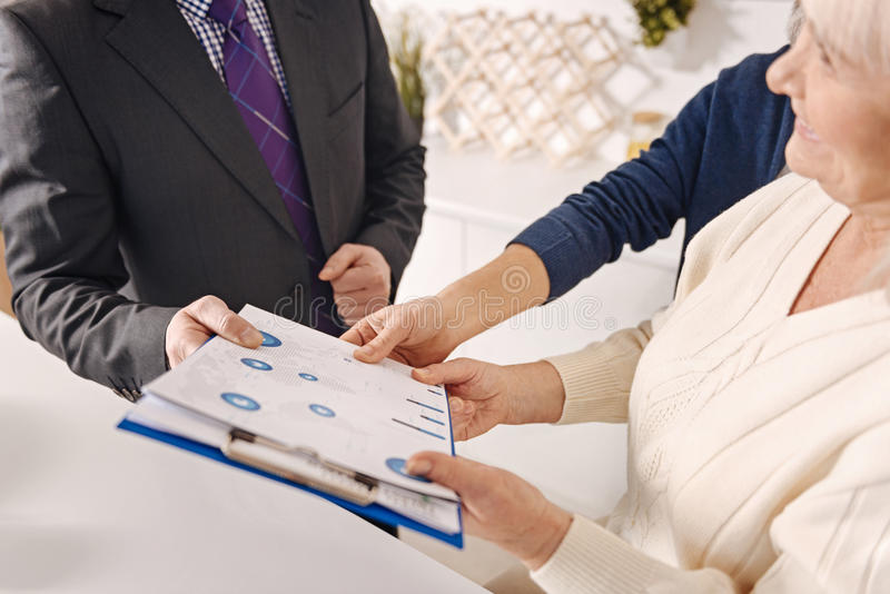Vrai agent immobilier professionnel faisant l'affaire avec les couples pluss âgé images stock