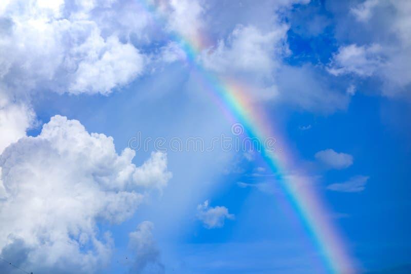 Vrai arc-en-ciel sur le ciel bleu avec le fond de nature de nuages photographie stock